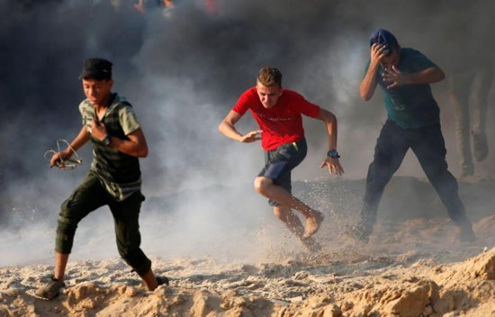 Palestinian youths run for cover from tear gas fired by Israeli troops during a Sept. 10 protest along a beach in the Gaza Strip. The U.S. budgetary cuts to humanitarian aid institutions providing assistance to Palestinians in Gaza and the West Bank could lead to long-term disastrous consequences, said aid workers in the region.