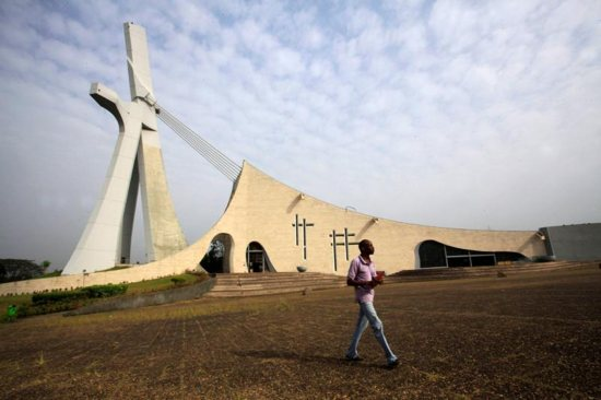 """A man walks outside the Cathedral of St. Paul in 2013 in Abidjan, Ivory Coast. African church leaders cautioned churchgoers against a false """"gospel of prosperity"""" after a bishop in Ivory Coast said it was gaining ground in Catholic parishes."""