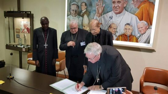 Archbishop Jean-Claude Hollerich, president of the Commission of the Bishops' Conferences of the European Union, signs a joint statement Oct. 26 at the Vatican's Sala Marconi calling on the international community to take immediate action against climate change. Also pictured in the signing are Also pictured in the signing are Archbishop Gabriel Mbilingi of Lubango, president of the Symposium of Episcopal Conferences of Africa and Madagascar, left, Cardinal Jose Luis Lacunza Maestrojuan of David, Panama, president of Latin American bishops' council's economic committee, and Cardinal Oswald Gracias of Mumbai, India, president of the Federation of Asian Bishops' Conferences.