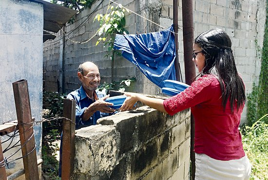 Dubraska Medina, a parishioner of Jesucristo Resucitado, delivers food to a man in need in San Félix, Venezuela.