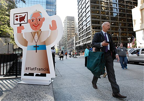 "Commuters pass a life-size ""Flat Francis"" in Daley Plaza in Chicago in 2015. Chicago-based Catholic Extension created the Flat Francis social media campaign to officially welcome Pope Francis on his first visit to America."