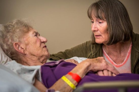 A woman sits at the bedside of her mother in 2016 at de Greeff Hospice house in St. Louis. This special house, the only one of its kind in St. Louis, serves terminally ill individuals.