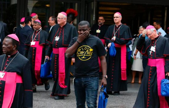 A youth delegate and bishops leave a session of the Synod of Bishops on young people, the faith and vocational discernment at the Vatican