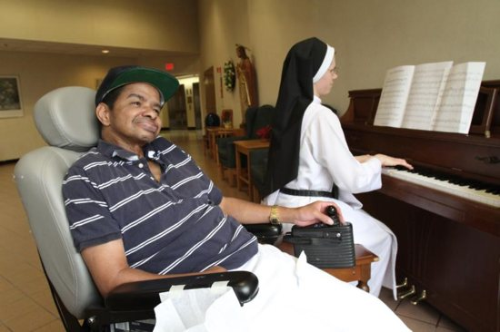 In this April 19, 2011, file photo, patient Warren Saunders smiles as Dominican Sister Agnes Mary plays the piano at Rosary Hill Home in Hawthorne, N.Y., where the nursing home staff provides palliative care to people with incurable cancer. Catholic experts have called for palliative care to become standard around the world.
