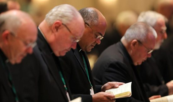 Bishop Shelton J. Fabre of Houma-Thibodaux, La., center, attends morning prayer Nov. 13 at the fall general assembly of the U.S. Conference of Catholic Bishops in Baltimore.