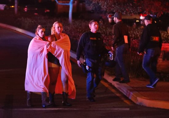 Two women draped in blankets leave the area near the Borderline Bar and Grill in Thousand Oaks, Calif., Nov. 8 after a gunman killed at least 13 people. The gunman, who opened fire without warning late Nov. 7, was found dead inside the establishment, authorities said.