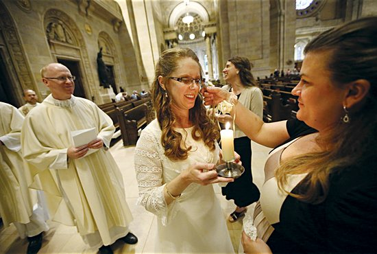 Susan Spiegelberg holds a candle she received during her consecration Mass June 8 at the Cathedral of St. Paul in St. Paul.