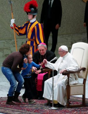 A mother retrieves her son after he wandered onstage during Pope Francis' general audience Nov. 28 in Paul VI hall at the Vatican. Seated at left is Archbishop Georg Ganswein, prefect of the papal household.