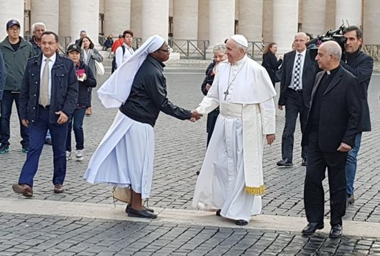 Pope Francis greets a woman religious as he makes a surprise visit to a free health clinic for the needy in St. Peter's Square at the Vatican Nov. 16. The clinic was open for a week in advance of the Nov. 18 observance of World Day for the Poor.