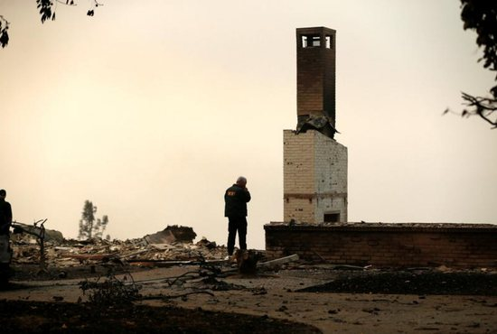 A Butte County Sheriff deputy surveys a home Nov. 11 that was destroyed by the Camp Fire in Paradise, Calif. Catholic schools in the Diocese of Sacramento are opening their doors to all students displaced by the fires to attend their schools tuition free for the rest of the year.