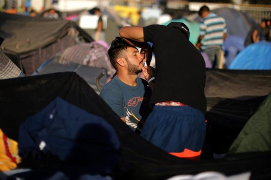 A migrant who is part of a caravan of thousands from Central America trying to reach the United States is groomed Nov. 27 at a temporary camp in Tijuana, Mexico. As concerns about the caravan rise, Bishop James A. Tamayo of Laredo, Texas, and other Texas bishops urged church leaders and lay faithful to extend respect and compassion for migrants and all who come to Catholic churches in need.