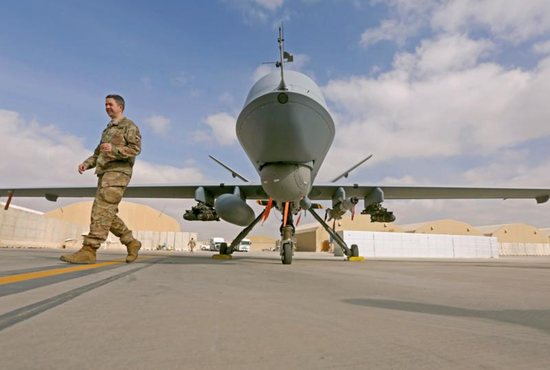 A U.S. service member passes in front of an MQ-9 Reaper drone to help to step up the fight against the Taliban at the Kandahar air base in Afghanistan.