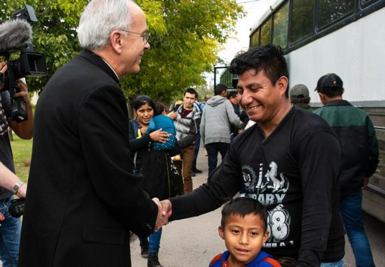 Bishop Mark J. Seitz of El Paso, Texas, greets immigrants Oct. 30 who arrived in the Diocese of El Paso on three buses.