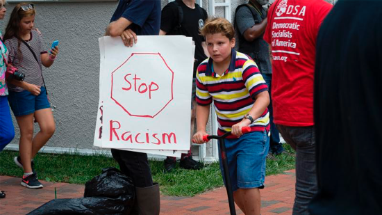 A person holds an anti-racism poster in Lafayette Square in Washington Aug. 12.