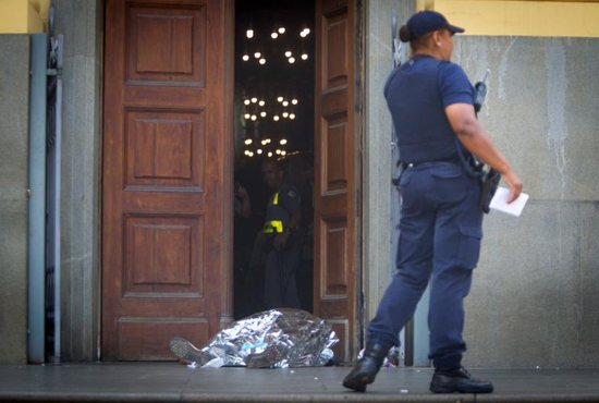 A police officer stands next to a body at the scene of a shooting Dec. 11 at the Metropolitan Cathedral in Campinas, Brazil. Police said Euler Fernando Grandolpho opened fire in the cathedral, killing at least four people and injuring several others before the 49-year-old turned the gun on himself after being shot by police.