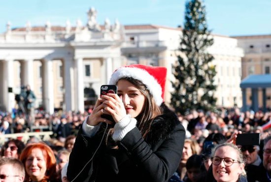 """A woman takes a photo before Pope Francis' Christmas message and blessing """"urbi et orbi"""" (to the city and the world) delivered from the central balcony of St. Peter's Basilica at the Vatican Dec. 25."""