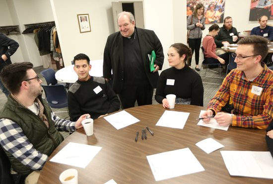 Archbishop Bernard Hebda talks with Tucker Moore, left, of the Basilica of St. Mary in Minneapolis, Christopher Damian of St. Thomas More in St. Paul, Kirby Hoberg of Holy Family in St. Louis Park, and Nathan Cornwell, also of Holy Family, before the start of a listening session for young adults Dec. 10 at the Archdiocesan Catholic Center in St. Paul.