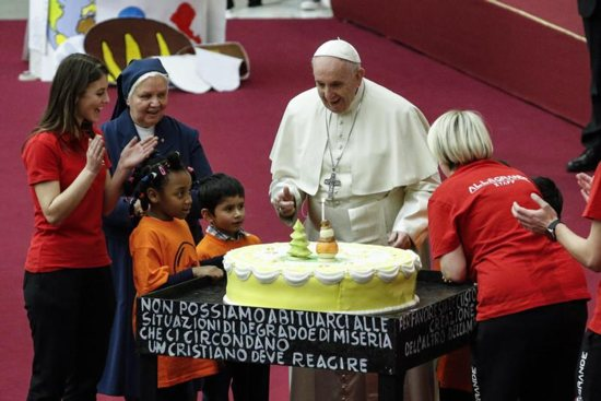 Pope Francis is presented with a cake on the eve of his 82nd birthday during a Dec. 16 audience with children and families from the Santa Marta Dispensary, a Vatican charity that offers special help to mothers and children in need.