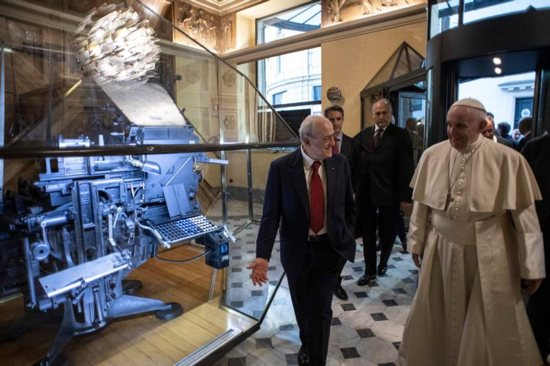 Pope Francis and Virman Cusenza, director of Il Messaggero daily newspaper, walk past a Linotype machine on display during a visit to the newspaper's office in Rome Dec. 8.