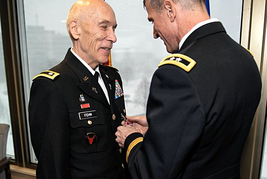 Father Jerome Fehn receives the Legion of Merit Medal Dec. 1 from Major General Neal Loidolt, deputy adjutant general of the Minnesota National Guard, at Joint Force Headquarters of the Army and Air National Guard in the Minnesota State Capitol in St. Paul.