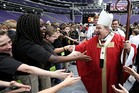 Archbishop Bernard Hebda greets Catholic elementary school students following the Mass of the Holy Spirit at U.S. Bank Stadium in Minneapolis