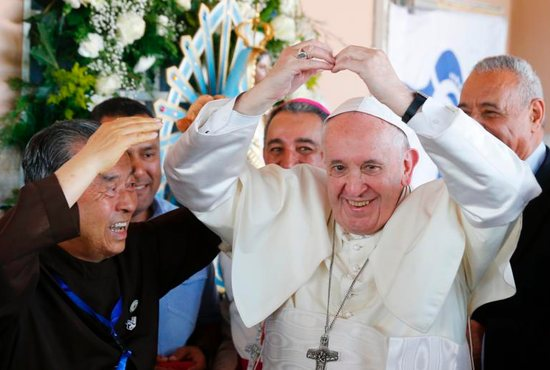 Pope Francis makes the shape of a heart as he visits Casa Hogar el Buen Samaritano (Good Samaritan Home) in Panama City Jan. 27, 2019. At left is Father John Oh Woong-Jin.