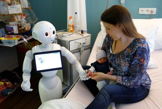 """""""Pepper"""" the robot, a humanoid robot designed to welcome and take care of visitors and patients, holds the hand of a new born baby next to his mother at AZ Damiaan hospital in Ostend, Belgium, June 16, 2016. The Vatican's Pontifical Academy for Life has added robotics to its list of specialized areas of study."""