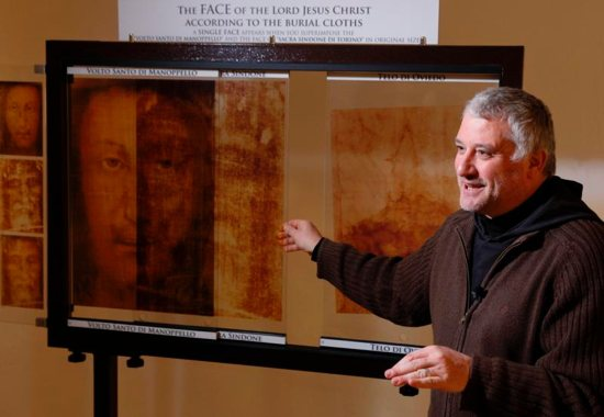 Capuchin Father Paolo Palombarini, parochial vicar of the Shrine of the Holy Face, explains the compatibility between the Holy Face of Manoppello and the Shroud of Turin as he overlays copies of the images in the museum at the shrine in Manoppello, Italy, Jan. 11. Devotees believe that the Holy Face of Manoppello was one of the burial shrouds that covered the face of Jesus in the tomb and that the image was formed miraculously at the moment of the resurrection.