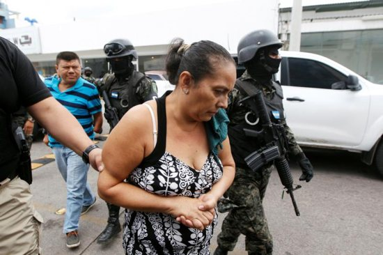 Investigative police agents escort suspected members of a human trafficking ring as they arrive to a court hearing in Tegucigalpa, Honduras, June 9, 2016.