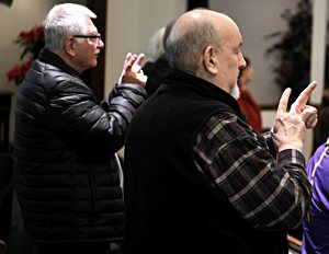 John Heinn of Andover, left, and Michael Hile of Minneapolis pray using American Sign Language at the Dec. 30 Mass.