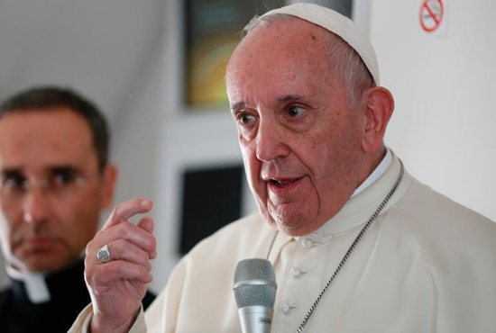 Pope Francis answers questions from journalists aboard his flight from Abu Dhabi, United Arab Emirates, to Rome Feb. 5, 2019. At left is Msgr. Mauricio Rueda, papal trip planner.