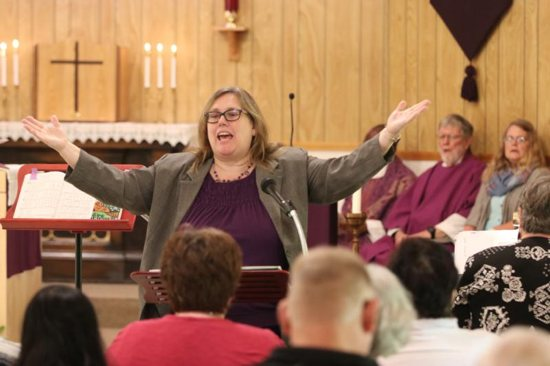 """Carol Fiel directs the choir and urges the congregation to join in during Mass in 2017 at St. John the Baptist Mission in Clatskanie, Oregon. Portland Archbishop Alexander K. Sample issued a new pastoral letter calling for sacred music characterized by sanctity, beauty and universality. """"Only music which possesses all three of these qualities is worthy of the holy Mass,"""" he wrote."""