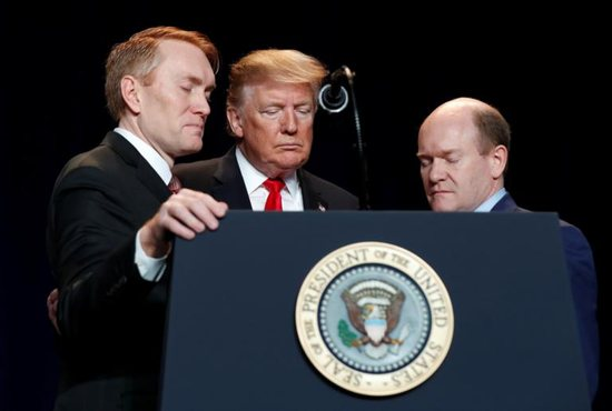 U.S. President Donald Trump joins Sens. James Lankford, R-Okla., and Chris Coons, D-Del., in prayer at the National Prayer Breakfast in Washington Feb. 7, 2019.
