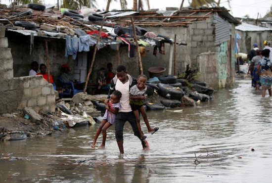 A man carries his children through floodwaters in the aftermath of Cyclone Idai in Beira, Mozambique, March 23, 2019. More than 2 million people in Mozambique, Zimbabwe and Malawi have been affected by a cyclone that has killed more than 700 people, with hundreds still missing in Mozambique and Zimbabwe.