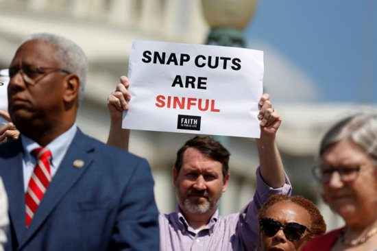 A man holds a sign protesting cuts to the federal Supplemental Nutrition Assistance Program during a news conference on Capitol Hill in Washington May 7, 2018. Catholic advocates planned to be involved in congressional budget hearings throughout the year to stress the importance of funding social and humanitarian programs that serve the common good.