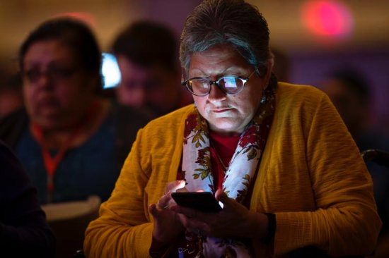 A delegate at the Fifth National Encuentro in Grapevine, Texas, checks the internet Sept. 21, 2018. Massgoers in Ireland are being urged to switch off their mobile phones during Lent.