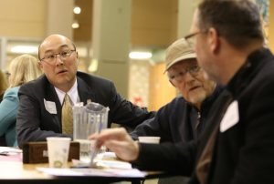 Ramsey County Attorney John Choi, left, talks Feb. 1 at St. Odilia Parish in Shoreview with Father Dan Griffith, foreground, pastor of Our Lady of Lourdes in Minneapolis, and Mark Umbreit, center, director of the Center for Restorative Justice and Peacemaking at the University of Minnesota in St. Paul.