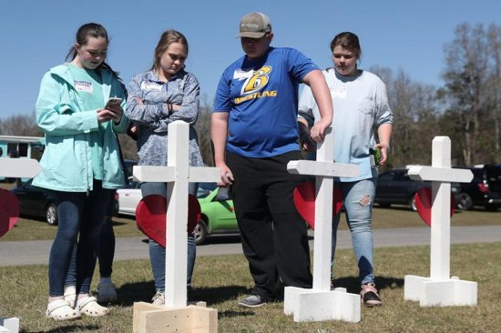 People in Beauregard, Ala., stand in front of crosses March 6, 2019, to honor the victims who died in the two tornadoes.