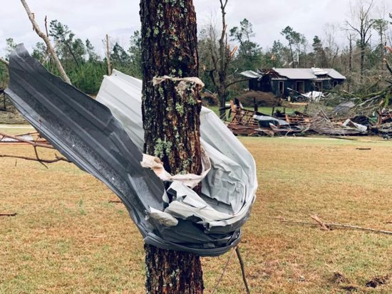 A piece of metal is seen wrapped around a tree following a tornado in Beauregard, Ala., March 3, 2019. At least 23 people were confirmed dead in Lee County, Ala.