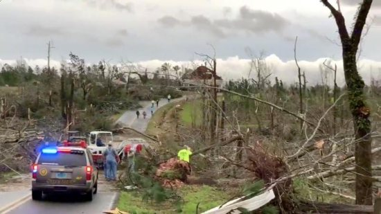 People clear fallen trees and debris on a road following a tornado in Beauregard, Ala., March 3, 2019. At least 23 were confirmed dead in Lee County, Ala.
