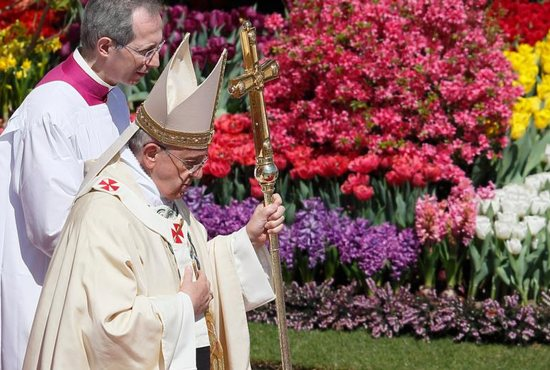Pope Francis walks past flowers as he leaves Easter Mass in St. Peter's Square at the Vatican April 20, 2014.