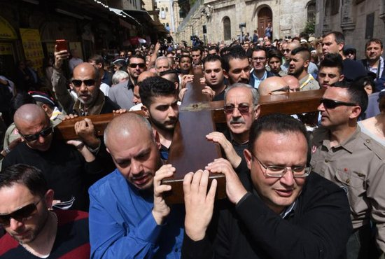 Mousa Kamar, front right, at the head of the cross, and his son Youssef, diagonal to his father, in the corner of the cross, helps carry a large wooden cross during the Good Friday procession on the Via Dolorosa in Jerusalem's Old City March 25, 2016. Mousa Kamar and his sons are carrying on the tradition of his grandfather and father, carrying the cross on Good Friday.