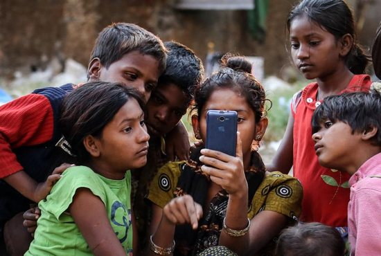 """Indian children watch a movie on a cellphone on the roadside in Mumbai Jan. 20, 2016. While digital communications and social media can be used as a tool of evangelization and a place of dialogue with others, they also can be lonely environments where young people fall prey to humanity's worst vices, Pope Francis wrote in his new apostolic exhortation to young people, """"Christus Vivit"""" (""""Christ Lives"""")."""