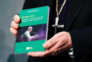 """Cardinal Lorenzo Baldisseri, secretary-general of the Synod of Bishops, holds Pope Francis' apostolic exhortation, """"Christus Vivit"""" (Christ Lives), during a news conference for its presentation at the Vatican April 2, 2019. The document contains the pope's reflections on the 2018 Synod of Bishops on young people, the faith and vocational discernment."""