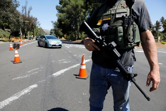 """A San Diego County Sheriff's Deputy secures the scene April 27, 2019, of a shooting incident at the Congregation Chabad synagogue in Poway, Calif., near San Diego. In response to the shooting, Cardinal Daniel N. DiNardo of Galveston-Houston and president of the U.S. Conference of Catholic Bishops, said in an April 28 statement: """"Our country should be better than this; our world should be beyond such acts of hatred and anti-Semitism."""""""