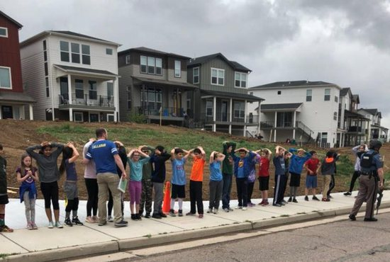 A photo obtained via social media shows school children standing in line with an armed police officer near STEM School Highlands Ranch during a shooting incident in at the Colorado school May 7, 2019. At least one student was killed and eight others injured in the shooting at the charter school in an affluent Denver suburb. Two suspects, both students at the school, were captured at the scene, authorities said. Two of the injured were listed in serious condition.
