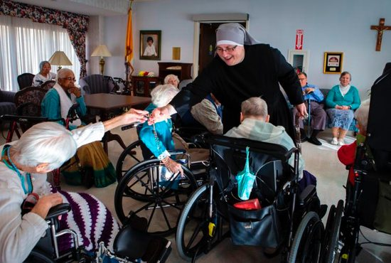 Sister Constance Veit, a Little Sister of the Poor, collects rosaries from elderly residents following prayers at the Jeanne Jugan Residence for senior care in Washington March 25, 2019. Sister Constance is considered a spiritual mother by many of the residents, who said they will honor her on Mother's Day.