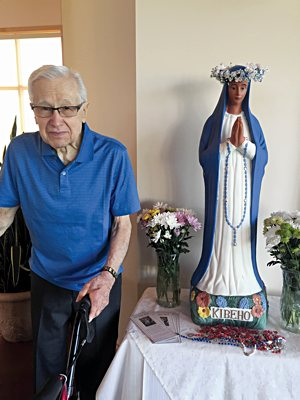 Matt Wiederkehr in 2015 with a statue of Our Lady of Kibeho at St. Genevieve in Centerville.