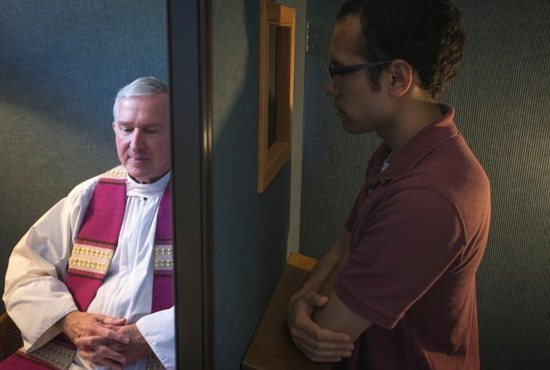 Father Timothy J. Mockaitis, pastor of Queen of Peace Catholic Church in Salem, Ore., and penitent Ethan K. Alano of Salem demonstrate how a confession is conducted May 3, 2019.