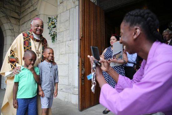 Washington Archbishop Wilton D. Gregory poses with two boys after celebrating Mass at St. Augustine Church in Washington June 2, 2019.